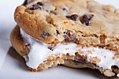 A chocolate chip sandwich cookie filled with cream with a bite taken out of it