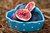 Fresh figs, whole and halved, in a heart-shaped bowl