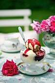 Vanilla ice cream with berry sauce on a table in the garden