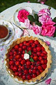 Strawberry tart and tea on a table in the garden