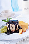 A mini cheesecake with chocolate sauce, grapes and nectarines