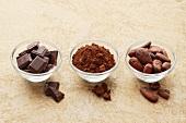 Schokoladenstücke, Kakaopulver und Kakaobohnen