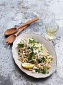 Warm pasta salad with salmon and parsley