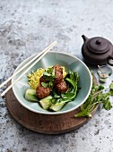 Meatballs with sesame seeds on a bed of vegetables served with noodles