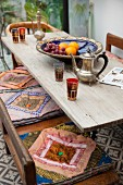 Holztisch mit orientalischer Teekanne und Gläsern und Holzbank mit bunten Sitzkissen