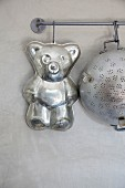 Bear-shaped cake tin and old metal colander hanging from butchers' hooks on metal rod