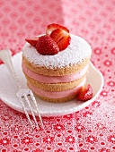 A strawberry tartlet with icing sugar