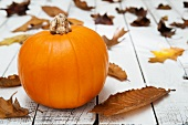 A pumpkin and autumnal leave on a wooden table