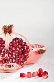 A pomegranate, halved and pomegranate seeds