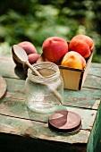 Offenes Schraubglas mit Holzlöffel und frische Pfirsiche auf einem kleinen rustikalen Tisch im Garten