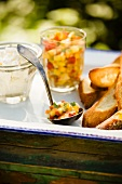 Ladle and Jar of Peach Salsa with Slices of Toasted Bread on a Tray on an Outdoor Table