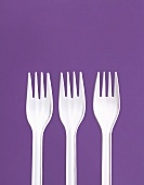 Three White Plastic Forks on a Purple Background