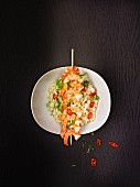 Risotto with a skewer of prawns, spring onions and chilli