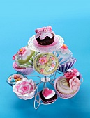 Romantic cupcakes decorated with flowers and hearts on a cake stand