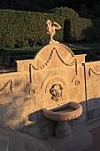 In Abendsonne getauchte Steinmauer mit Skulptur und eingearbeiteten Verzierungen über Brunnen in Gartenanlage