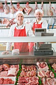 Smiling butchers standing next to meat in display case