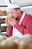 Baker smelling fresh bread from oven