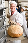 Baker removing fresh loaf of bread from oven