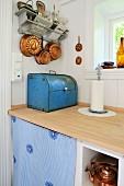 Vintage-Brotkasten und Koch-und Backutensilien aus Kupfer in renovierter Küche mit heller Arbeitsplatte aus Holz und weissen Holzwänden