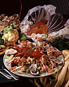 A platter of seafood with a mixture of crustaceans, oysters and vegetables