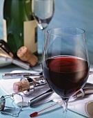 A glass of red wine and wine paraphernalia