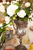 A bouquet of white roses in an old-fashioned silver vase as a table decoration