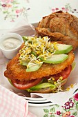 Schnitzel in a bun with avocado and edible shoots