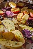 Peruanische Lila Kartoffeln und Fingerling-Kartoffeln, halbiert und gewürzt auf einem Backblech