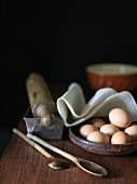 Organic Eggs in a Shallow Bowl; Wooden Spoons and Rolling Pin
