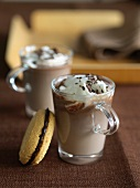 Two Cups of Hot Chocolate with Whipped Cream; Chocolate Filled Sandwich Cookie