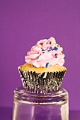 Lemon-filled blueberry cupcake with icing and sprinkles