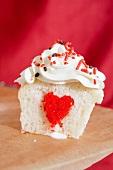 Cupcake mit Sahnecreme und rotem Herz in der Mitte