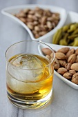 A glass of whisky with a ball of ice and a selection of nuts