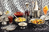 Partybuffet mit Getränken, Salat und Schweinefilet mit Orangen und Oliven