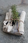 A napkin with a sprig of rosemary, dried blueberries and cutlery