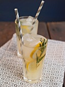 Two Glasses of Lemonade with Sprigs of Rosemary and Straws on a Wooden Table