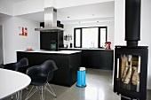Moderner Wohnraum in Schwarz Weiß - Essplatz mit Klassikerstühlen vor freistehendem Küchenblock und Kaminofen