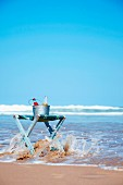An ice bucket with drinks on a folding stool at the beach
