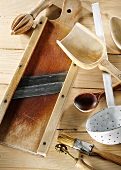 Kitchen utensils on a pale wooden surface