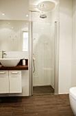 Modernes Designerbad mit abgetrenntem Duschbereich in Weiß mit braunen Bodenfliesen