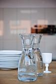 Gefüllte Wasserkaraffen neben Tellerstapel auf Tisch
