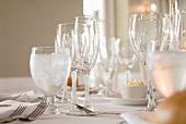 Verschiedene Stielgläser und Silberbesteck auf weisser Tischdecke