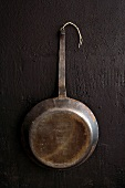 Vintage iron frying pan hanging on black wall