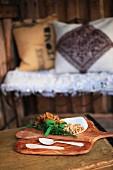 Pfifferlinge, Walnüsse und Kräuter mit Holzlöffeln auf Holzbrett; Drahtbank mit Kissen unscharf im Hintergrund