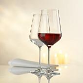 Zwei Weingläser, Stoffserviette und Kerzen