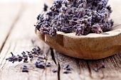 Lavender flowers in a wooden bowl on a wooden surface