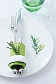 A plate decorated with a rosemary motif and a napkin ring decorated with a sprig of rosemary