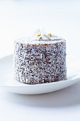 An individual coconut torte with candied daisies