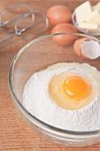 Aufgeschlagenes Ei auf Mehl in Glasschüssel, Eier, Butter, Rührbesen