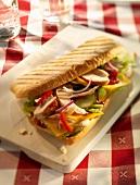 Baguettesandwich mit Hähnchen, Zwiebeln, Paprika, Essiggurken, Schmelzkäse, Salat und Ketchup auf Holzbrett